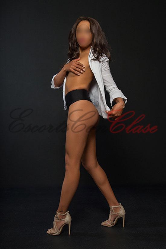 Amaya cubriendo su pecho desnudo con la mano. Una escort especialista en sexo anal