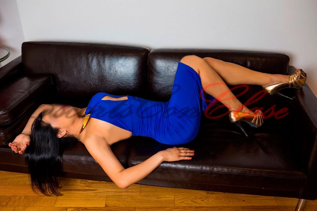 Escort vip Sevilla tumbada en sofá con un precioso vestido de noche azul. Laura