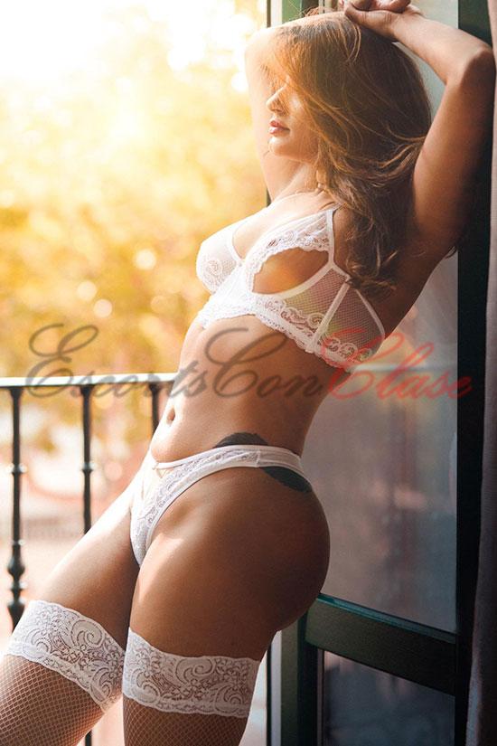 Escort de lujo rubia asomada a la ventana en lujosa lencería blanca. Adriana