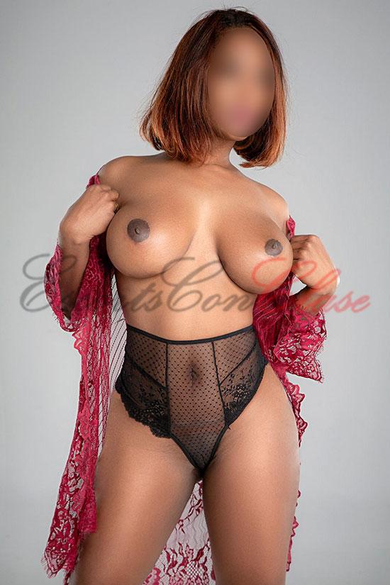 Joven acompañante de pelo rojizo muestra sus pechos desnudos. Aroa