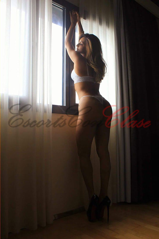 Escort rubia en lencería en la ventana. Vanessa