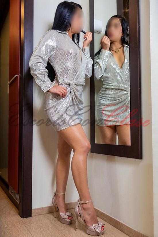 escort de lujo jovencita pintándose los labios ante el espejo. Natalia
